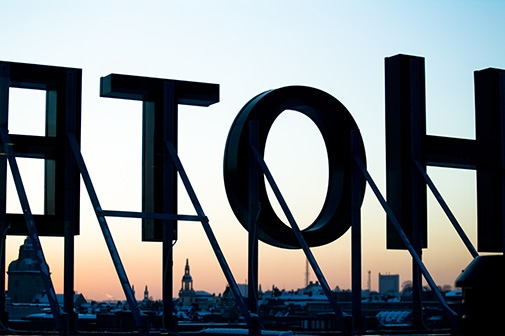Sign H O T E L L from behind with Stockholm sunset view in the background